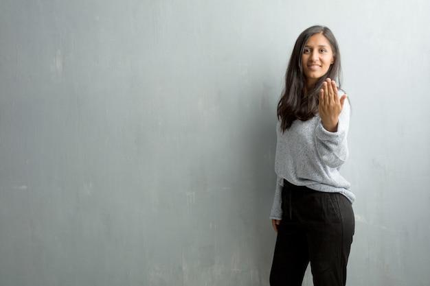 Junge indische frau gegen eine schmutzwand, die einlädt, zu kommen, überzeugt und lächelnd, eine geste mit der hand machend und positiv und freundlich seiend