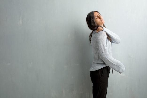 Junge indische frau gegen eine schmutzwand mit den rückseitigen schmerz wegen des arbeitsstresses