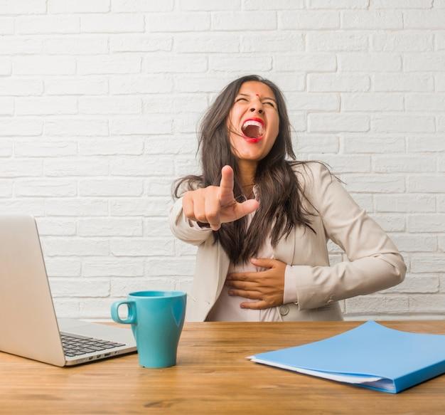 Junge indische frau im büro schreien, lachen und machen sich über andere, spottkonzept und unkontrolliertheit