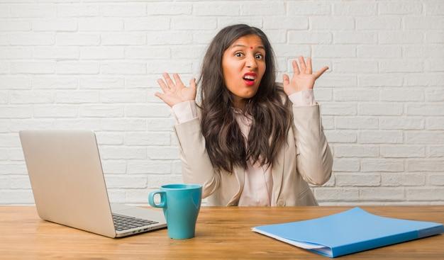 Junge indische frau im büro verrückt und verzweifelt, außerhalb der kontrolle schreien, lustige irres, die freiheit ausdrücken und wild