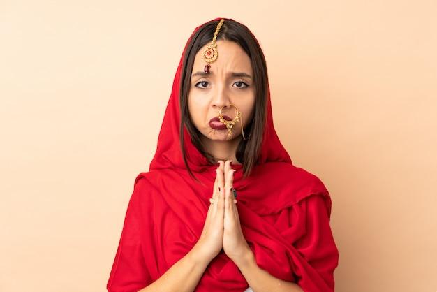 Junge indische frau isoliert auf beige hält handfläche zusammen. person fragt nach etwas