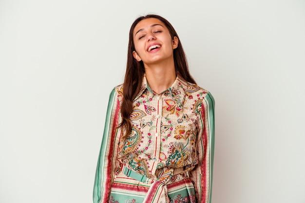 Junge indische frau isoliert auf weiß entspannt und glücklich lachend, hals gestreckt zeigt zähne.