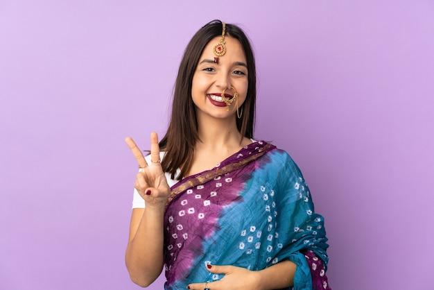 Junge indische frau isoliert lächelnd und siegeszeichen zeigend