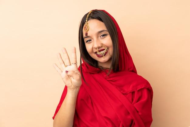 Junge indische frau lokalisiert auf beige glücklich und zählt vier mit den fingern
