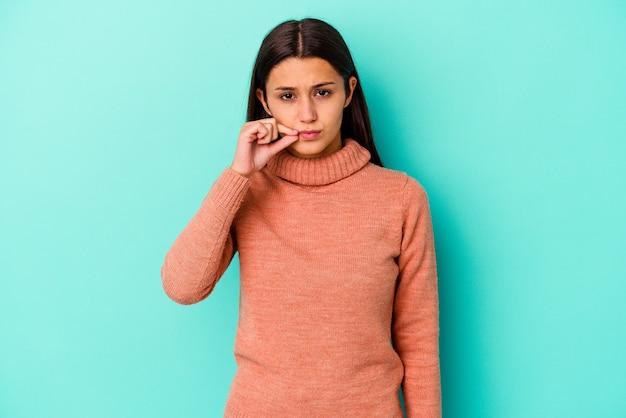 Junge indische frau lokalisiert auf blau mit den fingern auf den lippen, die ein geheimnis halten.