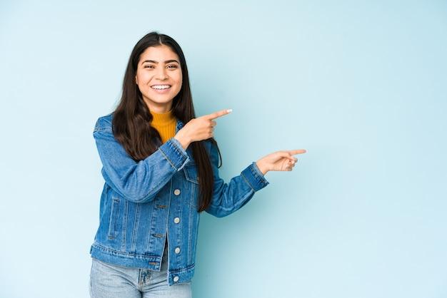 Junge indische frau lokalisiert auf blauem hintergrund aufgeregtes zeigen mit zeigefingern weg.