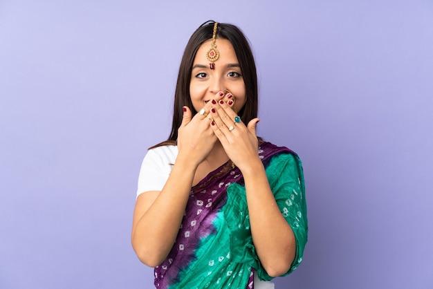 Junge indische frau lokalisiert auf lila bedeckendem mund mit händen