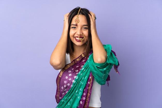 Junge indische frau lokalisiert auf lila, die nervöse geste tut