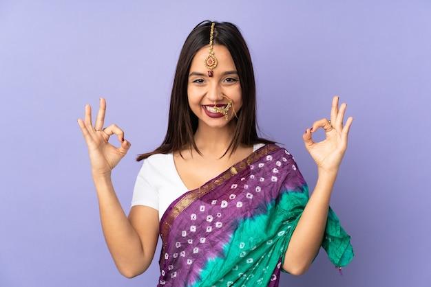 Junge indische frau lokalisiert auf lila hintergrund in zen-pose