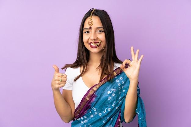 Junge indische frau lokalisiert auf lila wand, die ok zeichen und daumen hoch geste zeigt