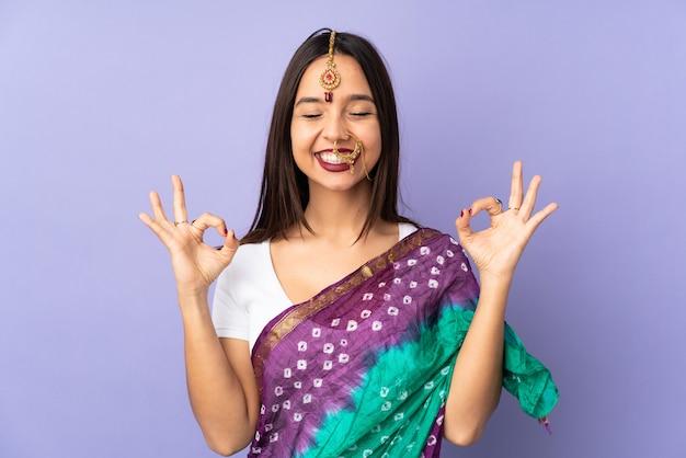 Junge indische frau lokalisiert auf lila wand in zen-pose