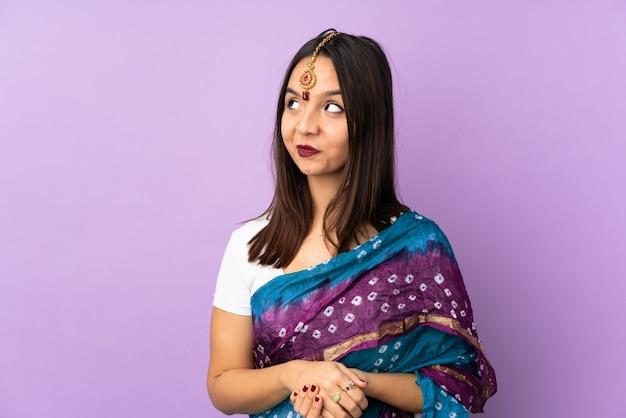 Junge indische frau lokalisiert auf purpur, der zweifel beim aufblicken hat