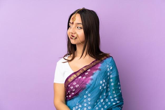 Junge indische frau lokalisiert auf purpur, der zweifel beim betrachten der seite hat