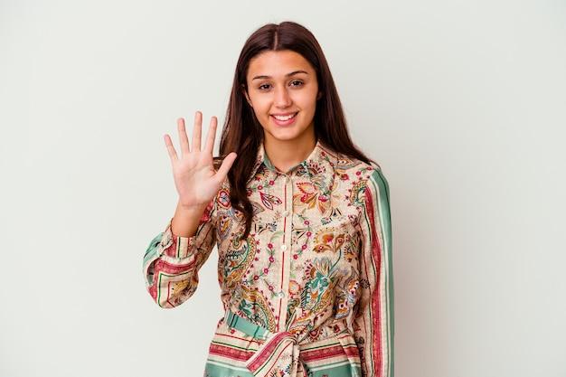 Junge indische frau lokalisiert auf weiß lächelnde fröhliche zeigende nummer fünf mit den fingern.