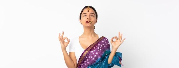Junge indische frau lokalisiert auf weißem hintergrund in zen-pose