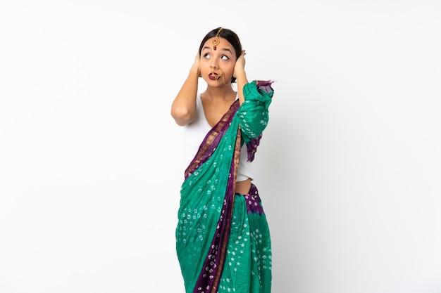 Junge indische frau lokalisiert auf weißen frustrierten und kegelnden ohren