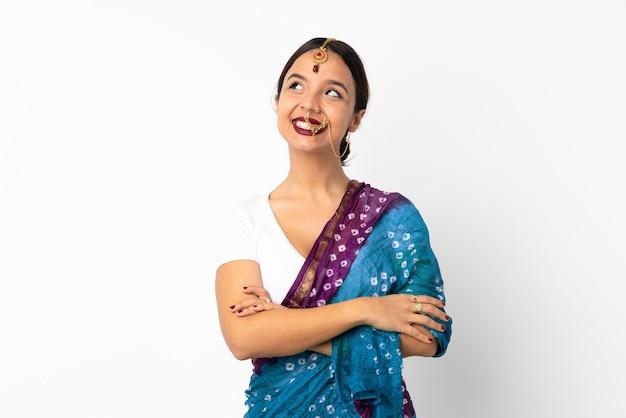 Junge indische frau lokalisiert auf weißer wand, die beim lächeln nach oben schaut