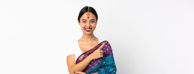 Junge indische frau lokalisiert auf weißer wand, die zur seite zeigt, um ein produkt zu präsentieren Premium Fotos