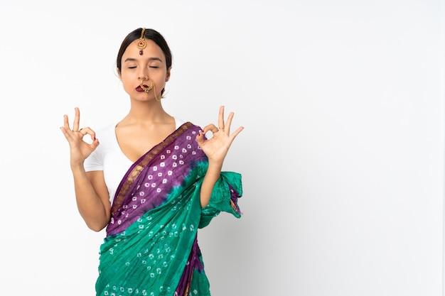 Junge indische frau lokalisiert auf weißer wand in zen-pose