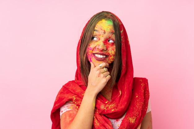 Junge indische frau mit bunten holi-pulvern auf ihrem gesicht auf rosa wand, die eine idee beim nachschlagen denkt