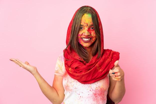 Junge indische frau mit bunten holi-pulvern auf ihrem gesicht auf rosa wand, die leerzeichen imaginär auf der handfläche hält, um eine anzeige und mit daumen hoch einzufügen