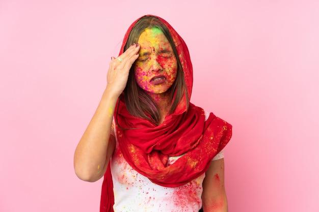 Junge indische frau mit bunten holi-pulvern auf ihrem gesicht auf rosa wand mit kopfschmerzen
