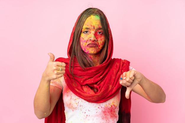 Junge indische frau mit bunten holipulvern auf ihrem gesicht auf rosa wand, die gutes-schlechtes zeichen macht