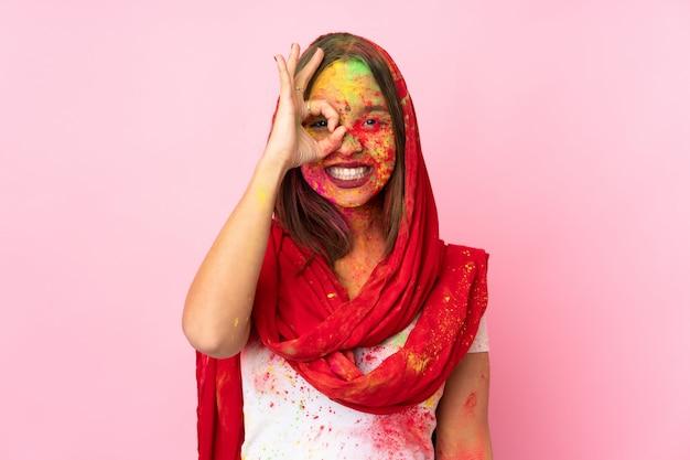Junge indische frau mit bunten holipulvern auf ihrem gesicht auf rosa wand, die ok zeichen mit den fingern zeigt