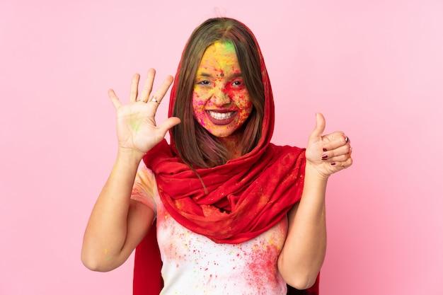 Junge indische frau mit bunten holipulvern auf ihrem gesicht auf rosa wand, die sechs mit den fingern zählt