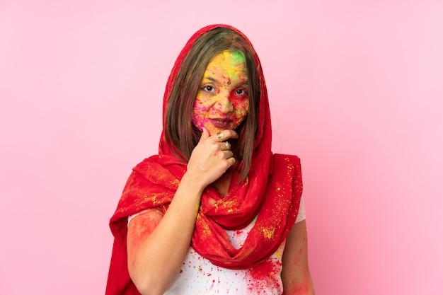 Junge indische frau mit bunten holipulvern auf ihrem gesicht auf rosa wanddenken