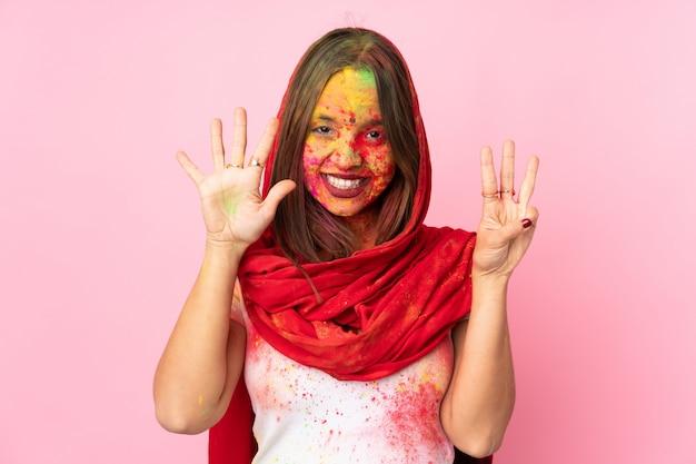 Junge indische frau mit bunten holipulvern auf ihrem gesicht lokalisiert auf rosa wand, die acht mit den fingern zählt