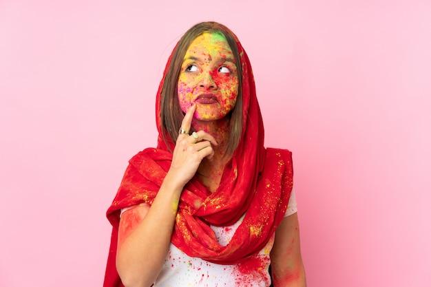 Junge indische frau mit bunten holipulvern auf ihrem gesicht lokalisiert auf rosa wand, die zweifel und denken hat