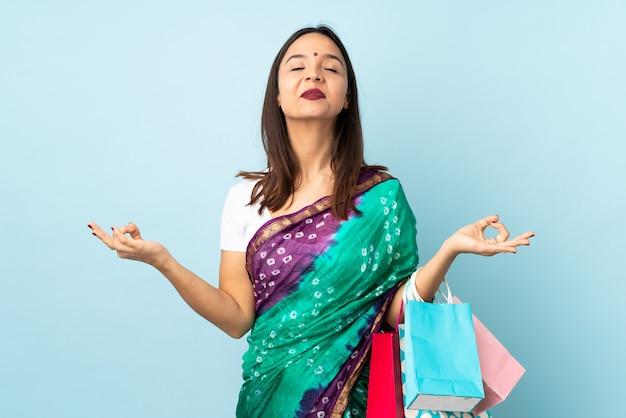 Junge indische frau mit einkaufstüten in zen-pose