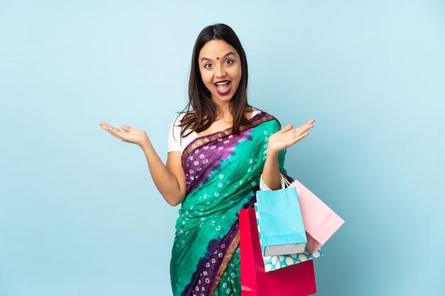 Junge indische frau mit einkaufstüten mit schockiertem gesichtsausdruck