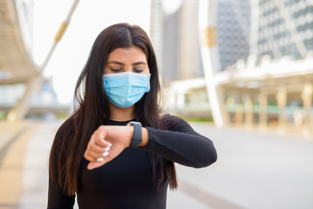 Junge indische frau mit maske, die die zeit an der skywalkbrücke prüft