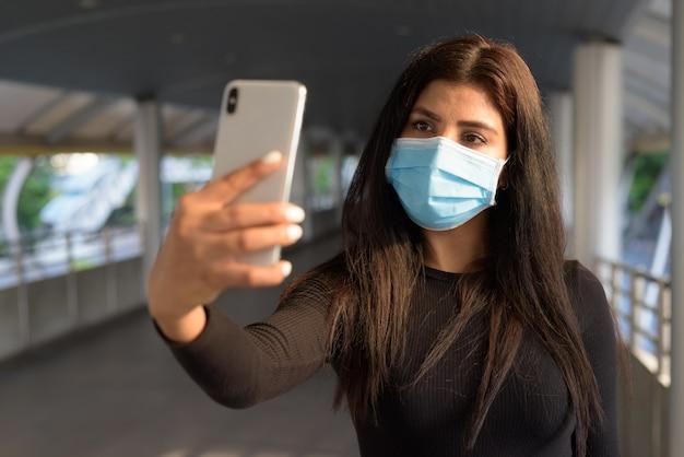 Junge indische frau mit maske, die selfie am steg nimmt