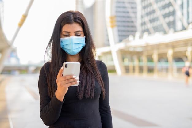 Junge indische frau mit maske unter verwendung des telefons an der skywalkbrücke