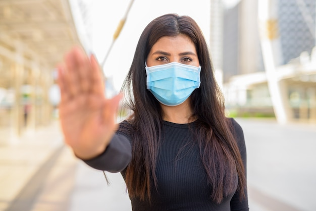 Junge indische frau mit maske zum schutz vor dem ausbruch des koronavirus, die stoppgeste in der stadt zeigt