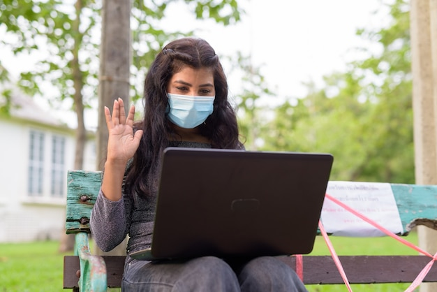Junge indische frau mit maskenvideoanruf beim sitzen mit abstand auf parkbank
