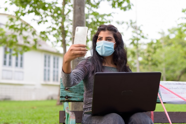 Junge indische frau mit maskenvideoanruf unter verwendung des telefons beim sitzen mit abstand auf parkbank