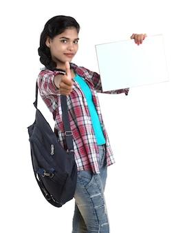 Junge indische frau mit rucksack stehend und hält weiße tafel, posierend.