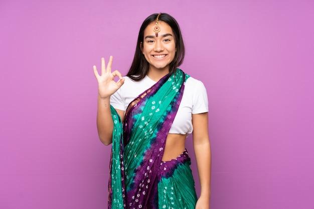 Junge indische frau mit sari über isolierter wand, die ok zeichen mit fingern zeigt