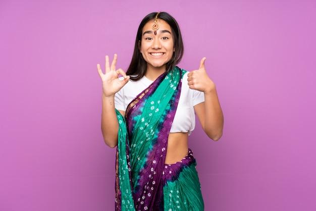 Junge indische frau mit sari über wand, die ok zeichen und daumen hoch geste zeigt