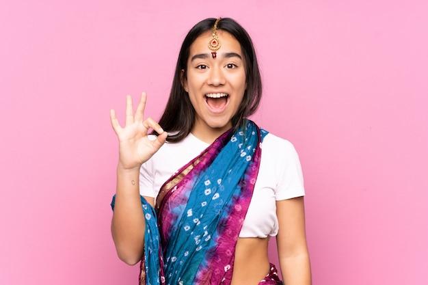 Junge indische frau mit sari über wand überrascht und zeigt ok zeichen
