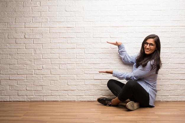 Junge indische frau sitzen gegen eine backsteinmauer, die etwas mit den händen hält, ein produkt zeigen, lächeln und nett und bietet einen eingebildeten gegenstand an