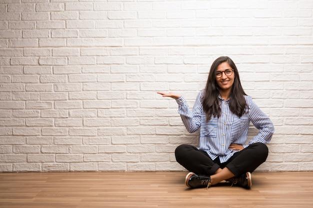 Junge indische frau sitzen gegen eine backsteinmauer, die etwas mit den händen hält und zeigen ein produkt