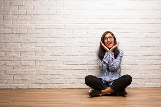 Junge indische frau sitzen gegen eine backsteinmauer, die überrascht und entsetzt ist und mit breiten augen schaut, aufgeregt durch ein angebot oder durch einen neuen job, gewinnkonzept