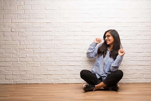 Junge indische frau sitzen gegen eine backsteinmauer musik hören