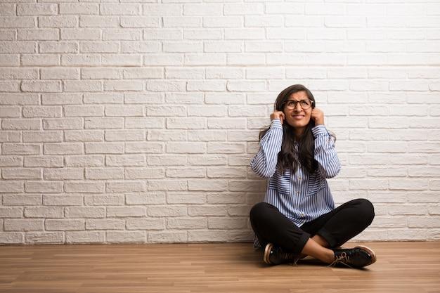 Junge indische frau sitzen gegen ohren einer backsteinmauerbedeckung mit den händen