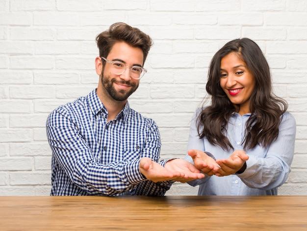 Junge indische frau und kaukasische mannpaare, die etwas mit den händen halten, ein produkt zeigen, lächeln und nett und bieten einen eingebildeten gegenstand an